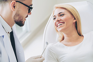 Smiling woman seated in a dental chair discusses dental procedures with her dentist