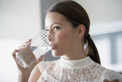 A woman drinking from a glass of water.