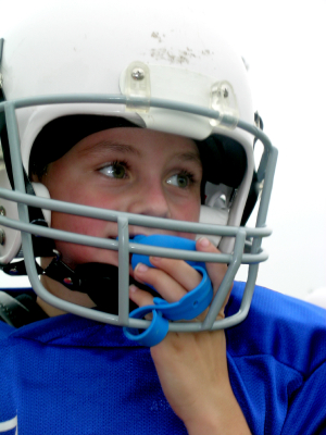 A young boy in a football uniform using a mouth guard.